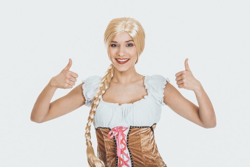 Femme dans la robe bavaroise avec des pouces  images libres de droits