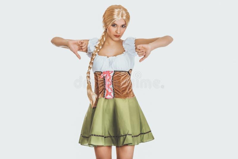 Femme dans la robe bavaroise avec des pouces vers le bas photographie stock libre de droits
