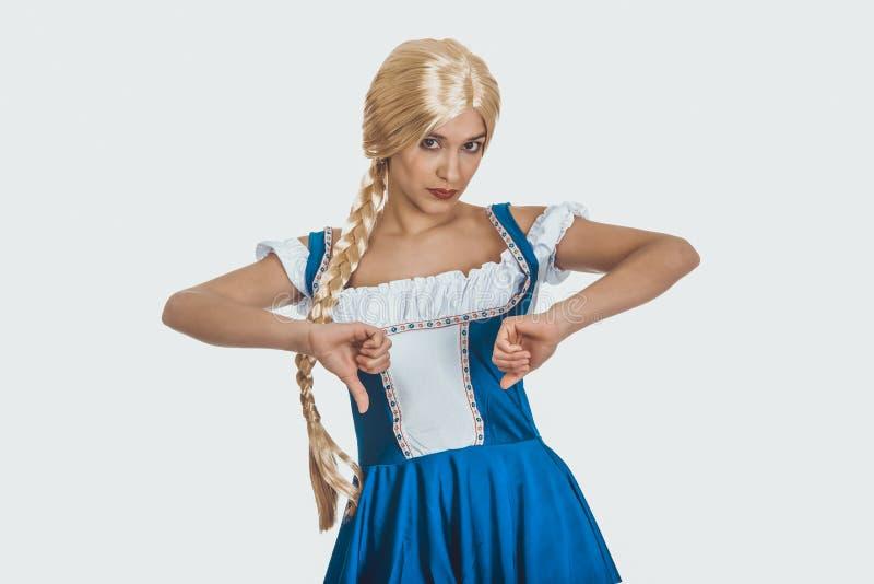 Femme dans la robe bavaroise avec des pouces vers le bas photo stock