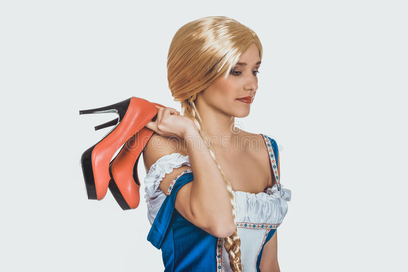 Femme dans la robe bavaroise tenant ses chaussures photos stock