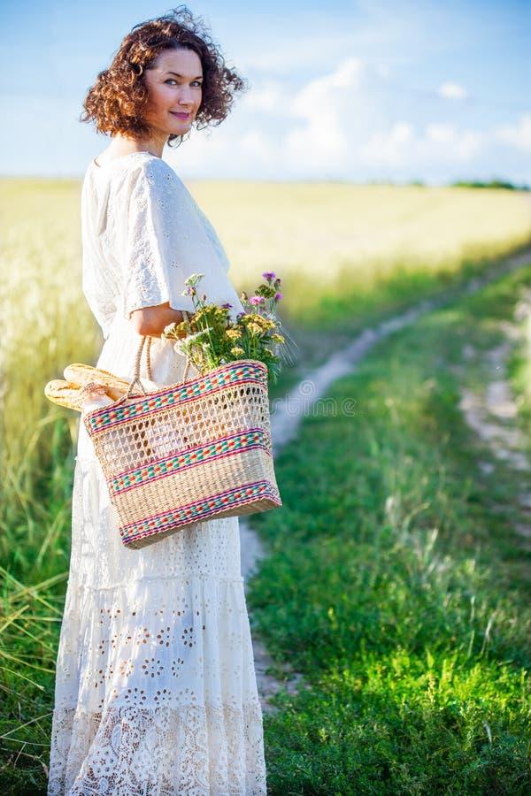 Femme dans la robe blanche avec le panier avec du pain et le lait alo de marche images stock