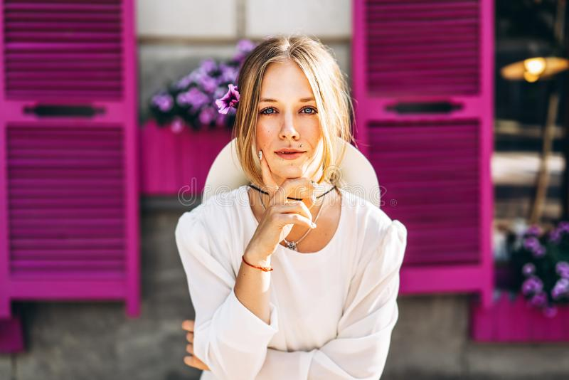 Femme dans la robe blanche de vintage sur la rue avec les fenêtres pourpres b image libre de droits