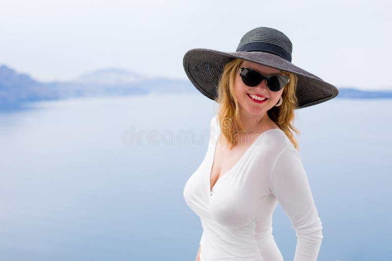 Femme dans la robe blanche et le chapeau noir images stock