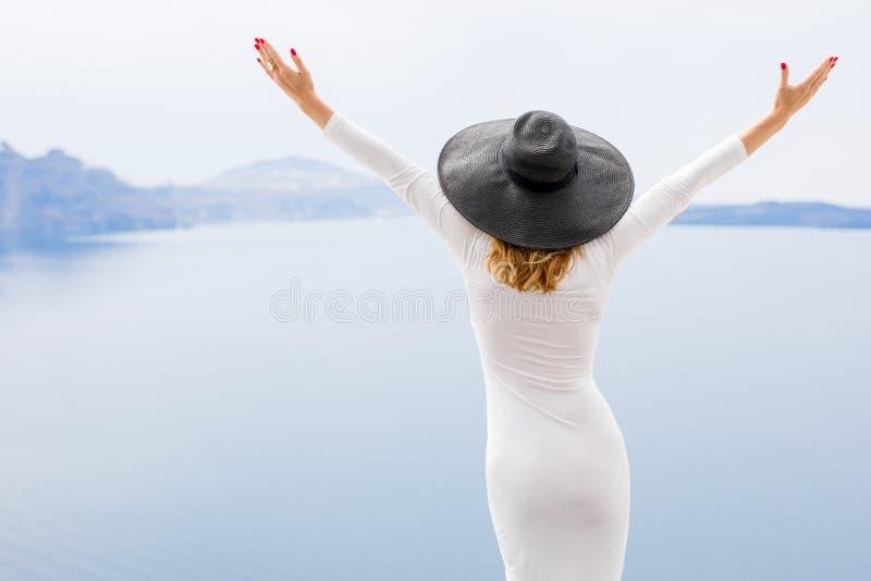 Femme dans la robe blanche et le chapeau noir aux vacances image libre de droits