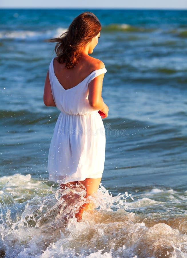 Femme dans la robe blanche posant sur une plage de mer photo libre de droits