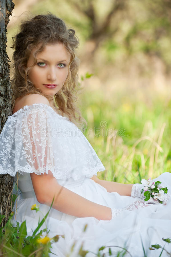 Femme dans la robe blanche se reposant sur l'herbe image stock