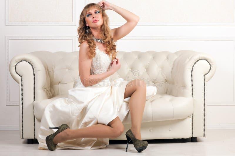 Femme dans la robe blanche se reposant sur un sofa image stock