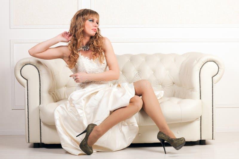 Femme dans la robe blanche se reposant sur un sofa photos stock