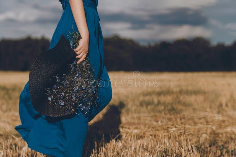 Femme dans la robe bleue avec un chapeau dans ses promenades de main et de bouquet autour du champ jaune photo libre de droits