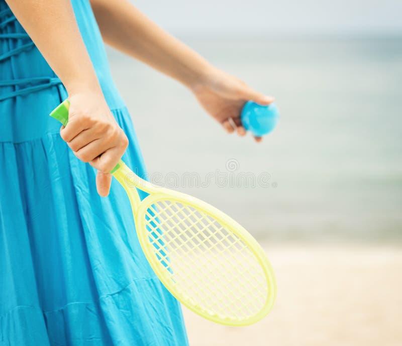 Femme dans la robe bleue jouant le tennis sur la plage image libre de droits