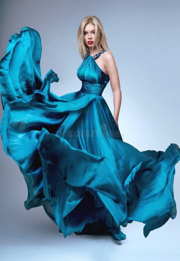 Femme dans la robe bleue posant à l'appareil-photo image libre de droits