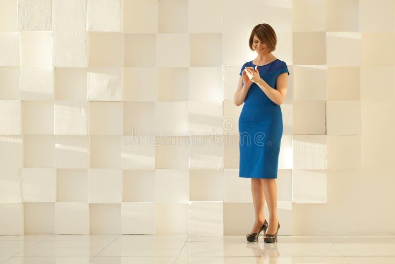 Femme dans la robe bleue se tenant contre le mur moderne tout en regardant le smartphone photo libre de droits