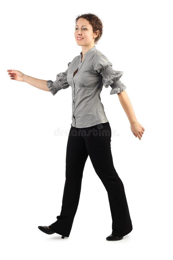 Femme dans la robe d'affaires marchant à gauche et souriant photographie stock libre de droits