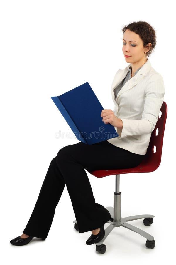 Femme dans la robe d'affaires se reposant sur la présidence photos stock