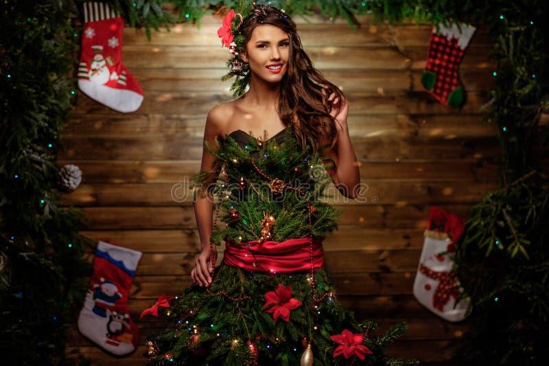 Femme dans la robe d'arbre de Noël avec le verre du champagne et du cierge magique images stock