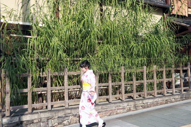 Femme dans la robe de kimono marchant sur l'arbre en bambou de passage couvert et de fond avec la barrière en bois photo stock