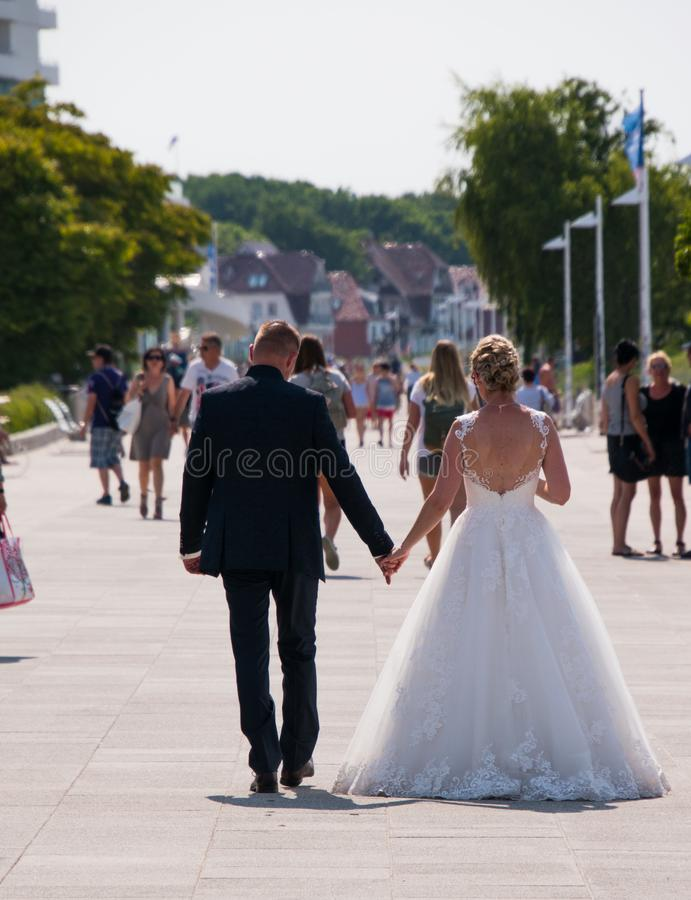 Femme dans la robe de mariée et l'homme dans le smoking marchant sur le trottoir dans cette ville de touristes ensuite s'étant ma photo stock