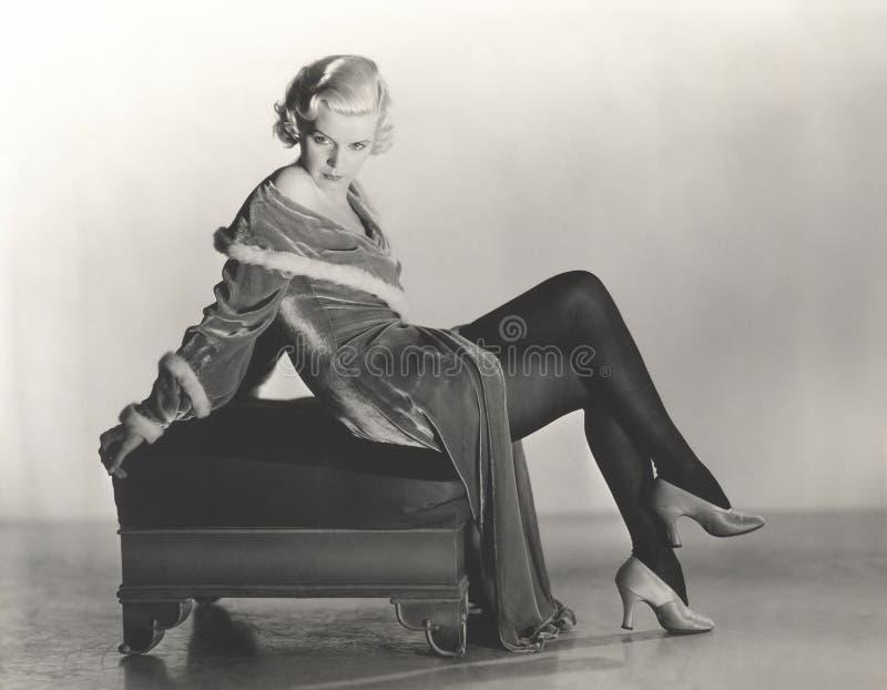 Femme dans la robe de velours se reposant sur le tabouret images libres de droits