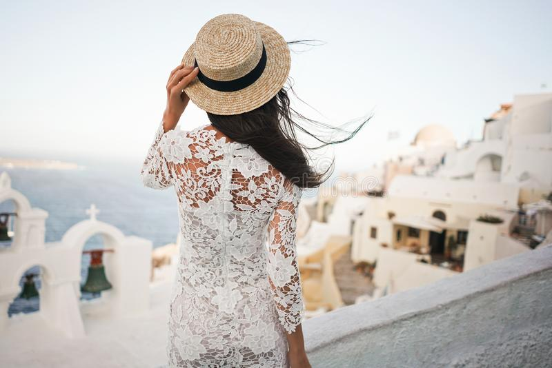 Femme dans la robe et le chapeau de paille blancs sur l'île de Santorini image libre de droits