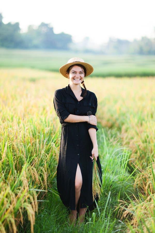 Femme dans la robe et le chapeau de paille noirs images stock