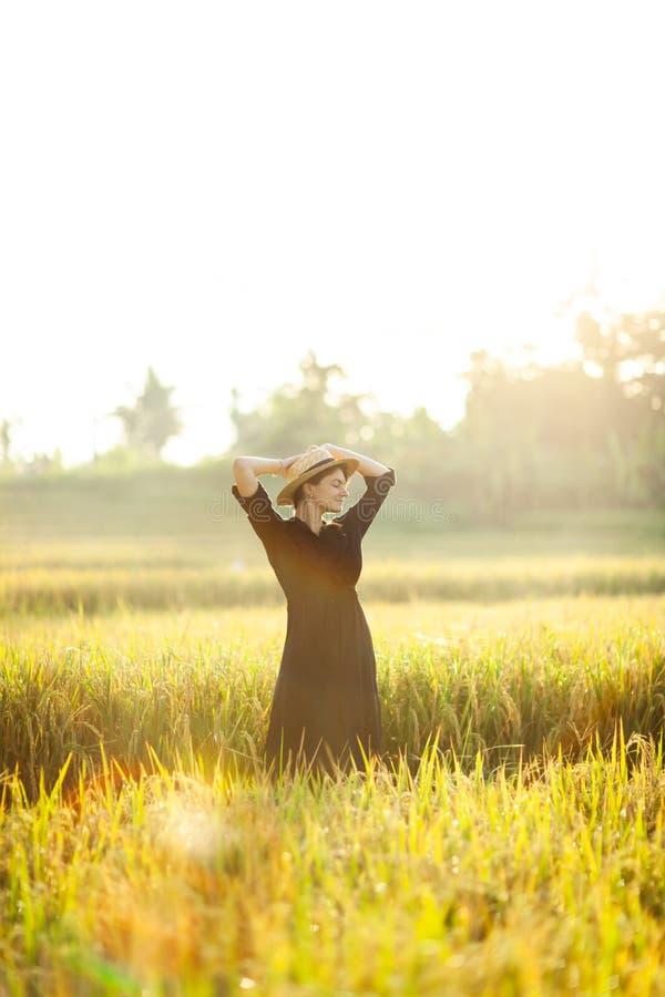 Femme dans la robe et le chapeau de paille noirs image libre de droits