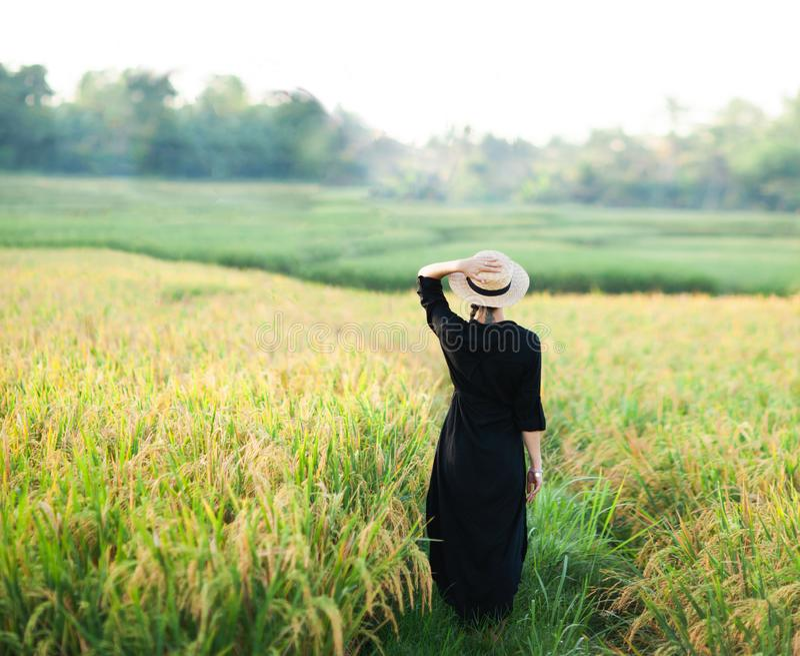 Femme dans la robe et le chapeau de paille noirs image stock