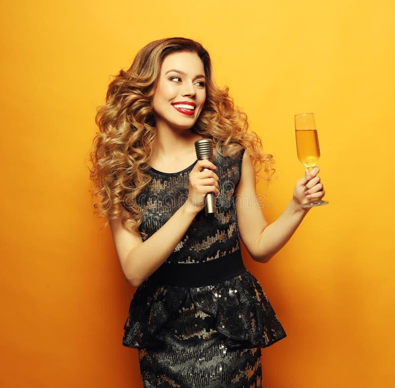 femme dans la robe ?galisante noire tenant le verre du champagne et du microphone Pr?parez pour la partie de karaoke images stock