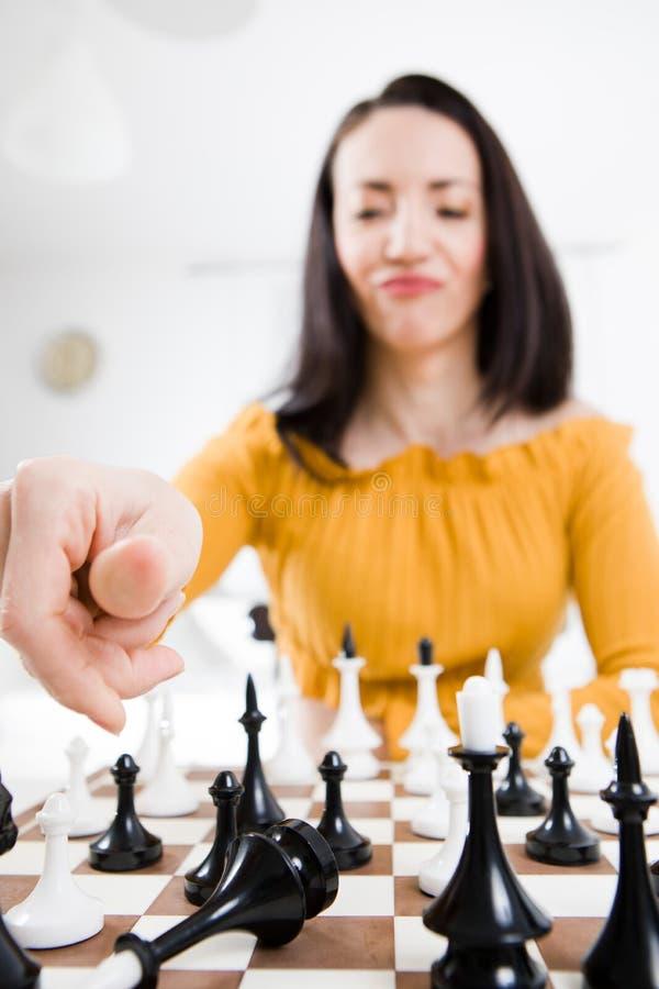 Femme dans la robe jaune se reposant devant des échecs - compagnon de contrôle images stock