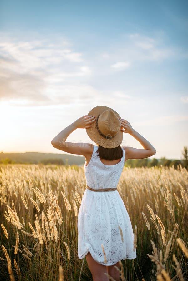 Femme dans la robe marchant dans le domaine de blé sur le coucher du soleil images libres de droits