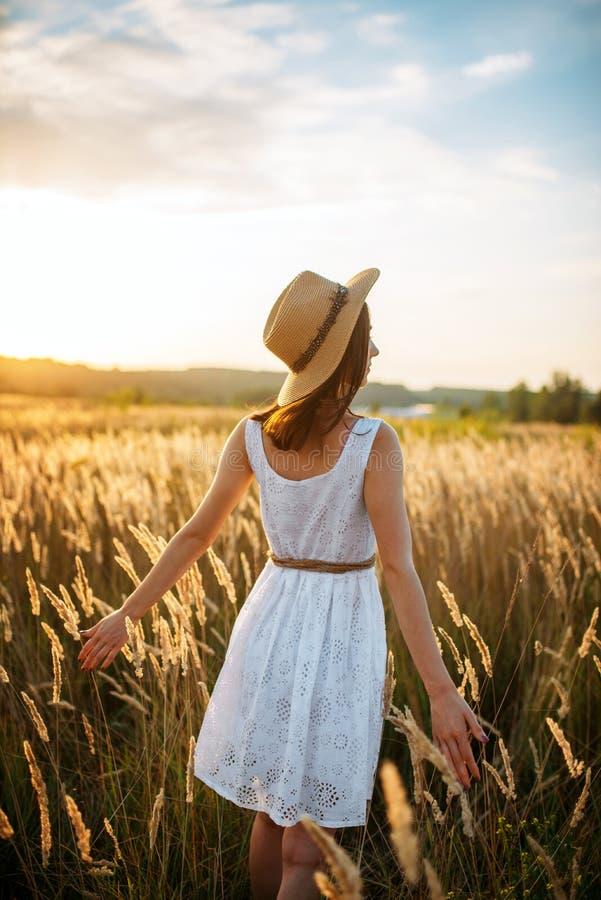 Femme dans la robe marchant dans le domaine de blé sur le coucher du soleil photo libre de droits