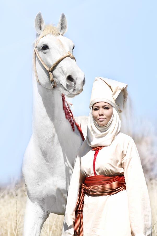 Femme dans la robe nationale blanche asiatique avec le cheval blanc en nature photo libre de droits