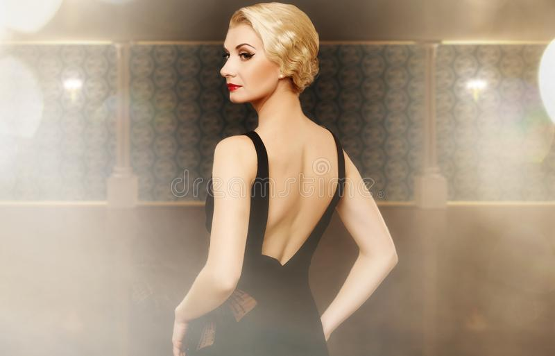 Femme dans la robe noire à l'intérieur images stock