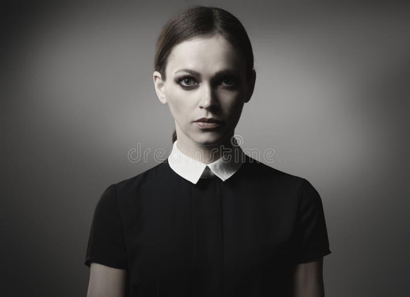 Femme dans la robe noire avec intellectuel images stock