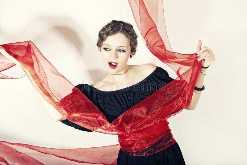 Femme dans la robe noire avec la ceinture rouge photographie stock libre de droits