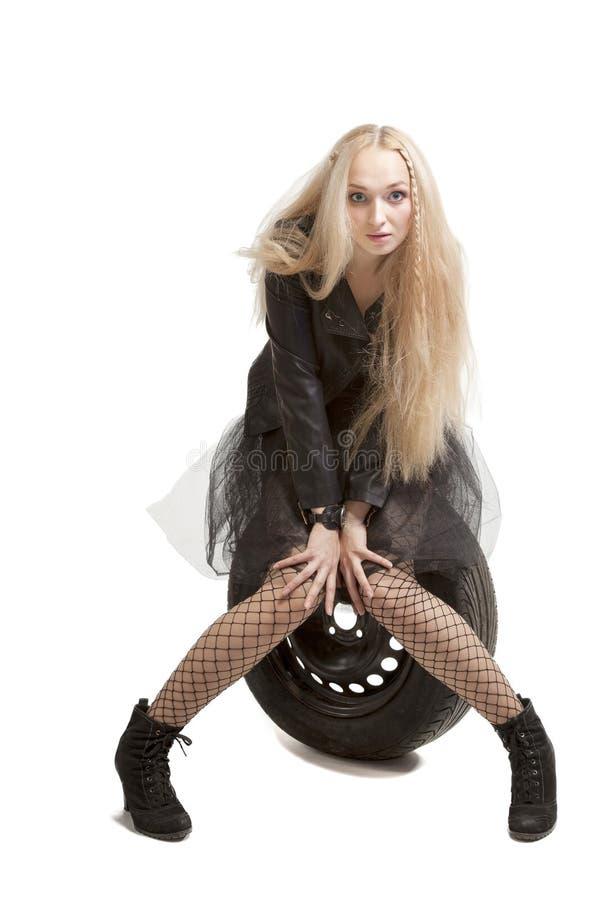 Femme dans la robe noire avec le pneu de voiture images stock