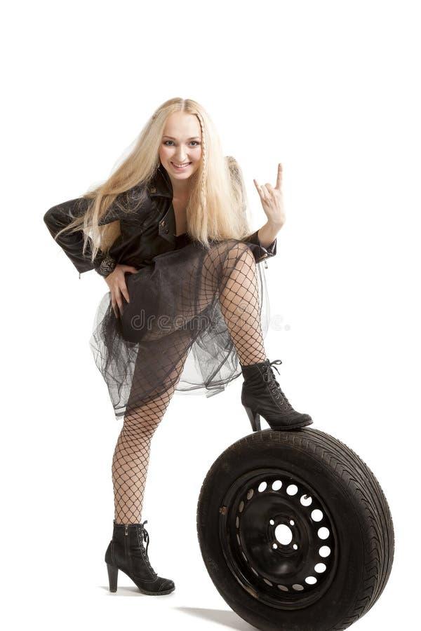 Femme dans la robe noire avec le pneu de voiture photo libre de droits