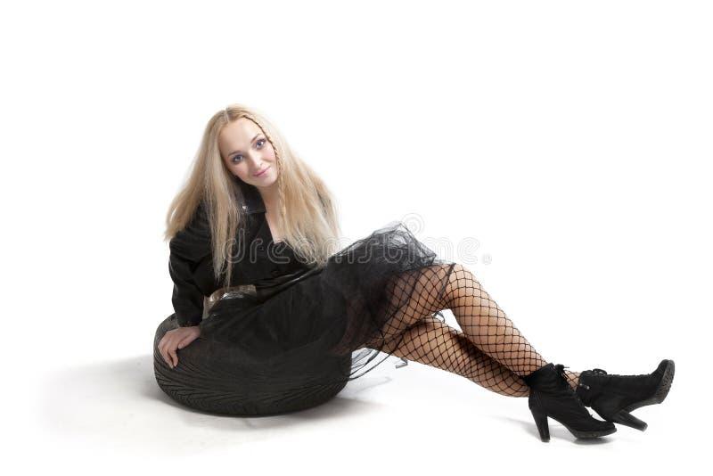 Femme dans la robe noire avec le pneu de voiture photo stock