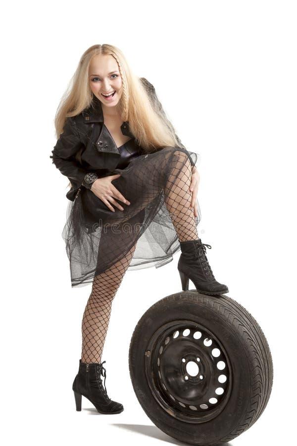 Femme dans la robe noire avec le pneu de voiture photos stock