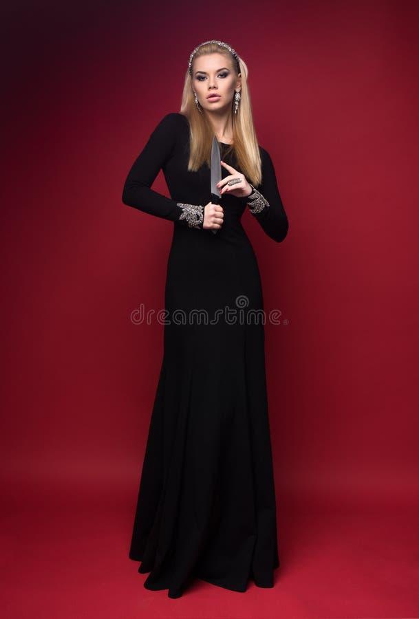 Femme dans la robe noire avec un couteau photographie stock libre de droits