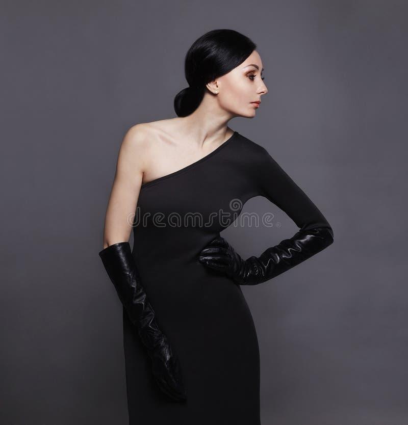 Femme dans la robe noire et les gants en cuir images stock