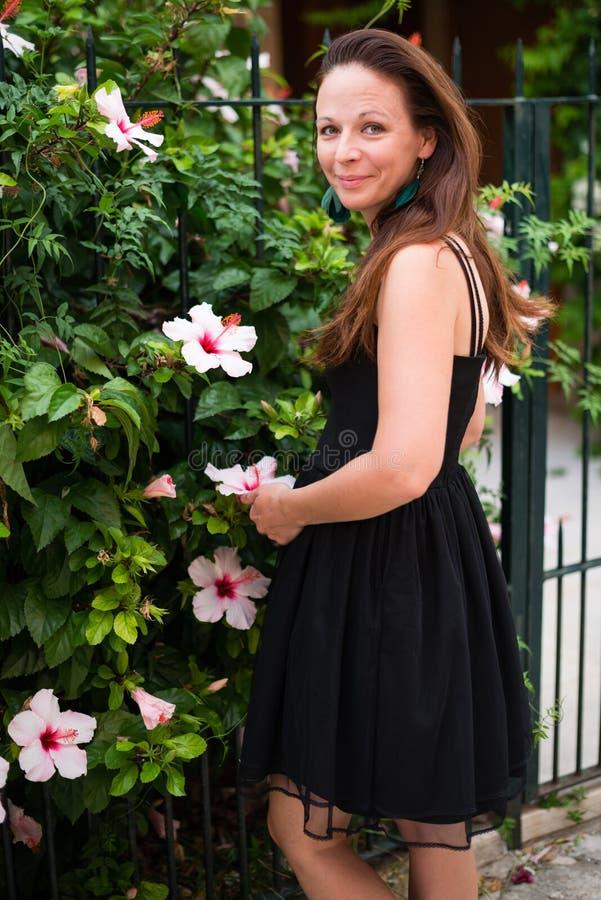Femme dans la robe noire posant avec des fleurs photographie stock libre de droits