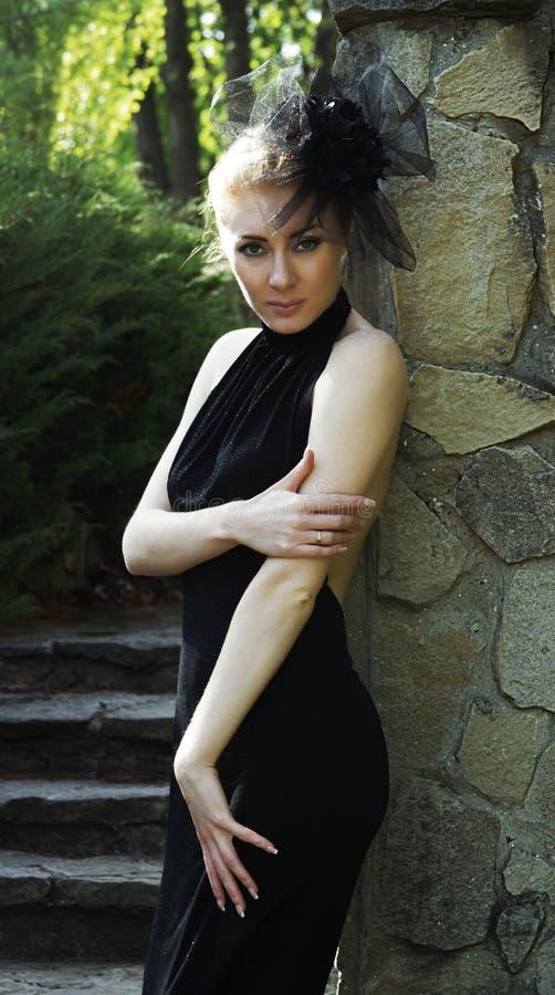Femme dans la robe noire près du mur en pierre images stock