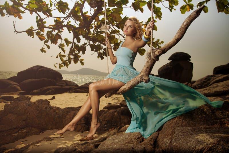 Femme dans la robe oscillante bleue balançant sur une plage Swi photographie stock