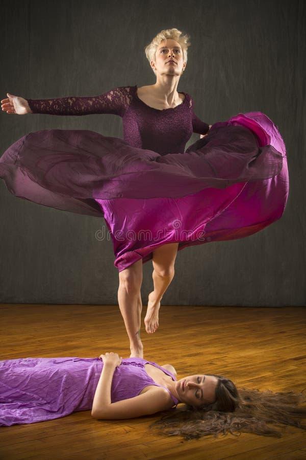 Femme dans la robe pourpre dansant au-dessus de l'ami sur le plancher photographie stock