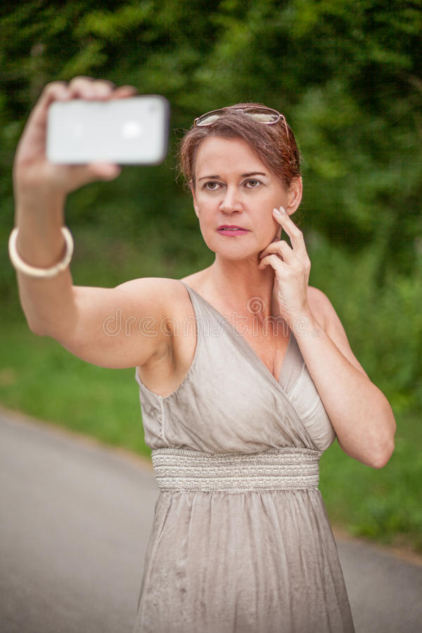 Femme dans la robe prenant l'autoportrait avec le téléphone portable photographie stock libre de droits