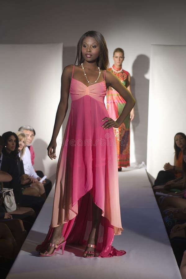 Femme dans la robe rose sur la passerelle de mode image libre de droits