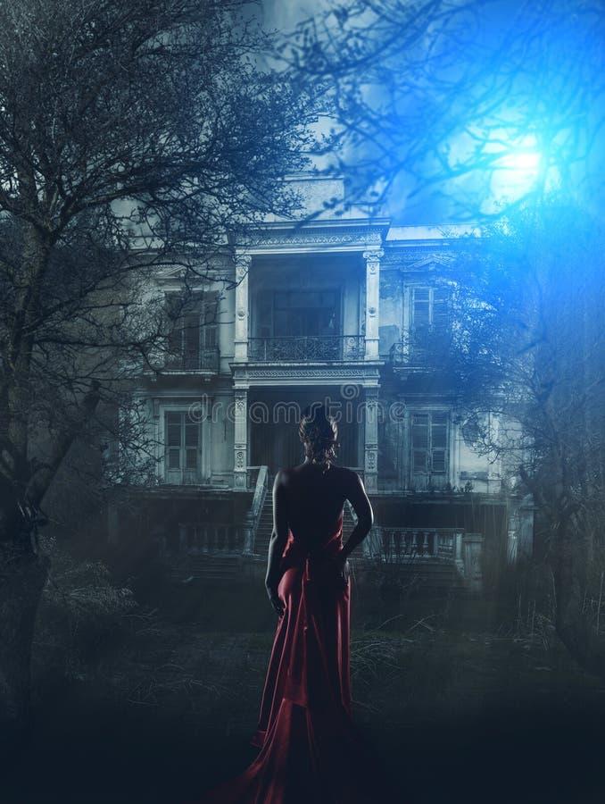 Femme dans la robe rouge à la maison hantée photos stock