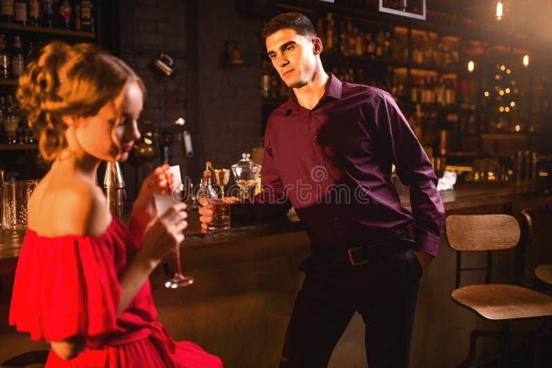 Femme dans la robe rouge avec le cocktail à disposition, flirtant photo stock
