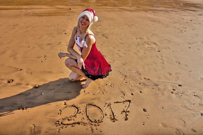 Femme dans la robe rouge avec le dessin sur les chiffres 2017 de sable photo libre de droits