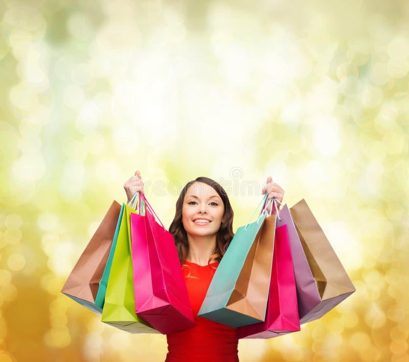 Femme dans la robe rouge avec les paniers colorés images stock